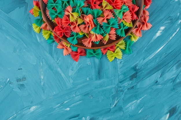 Pile of colorful raw farfalle pasta on blue background.