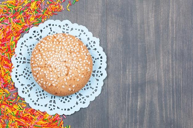 Pila di granelli colorati intorno a un gustoso biscotto