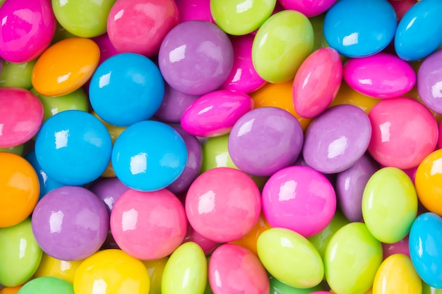 Pile of colorful sweet candy chocolates coated on white paper. colourful collection background