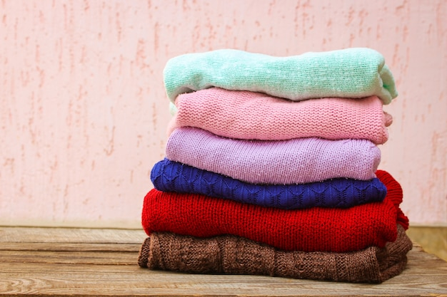 Pile of colorful warm clothes on wooden table.