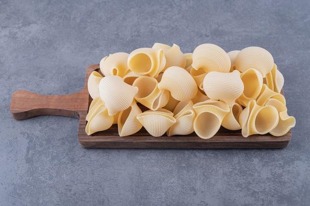 Pila di pasta conchiglie su tavola di legno.