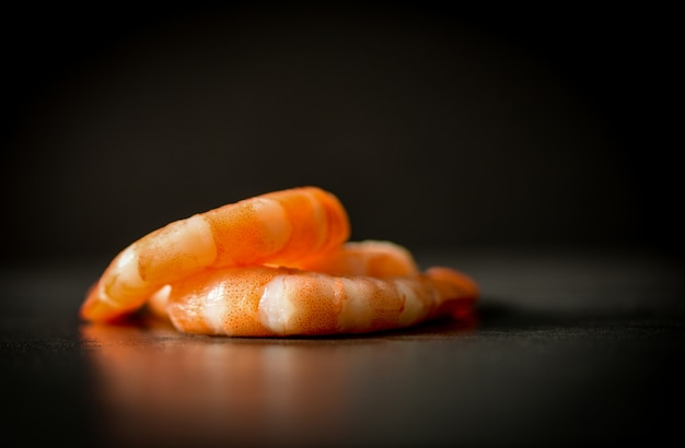 Pile of cooked seafood shrimps prawns on black dark background