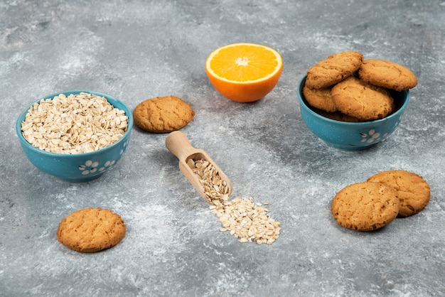 Pile of cookie and oatmeal in a bowl and half-cut orange over grey surface.
