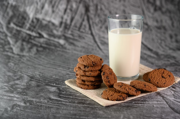 A pile of cookies and a glass of milk on a cloth on a wooden table