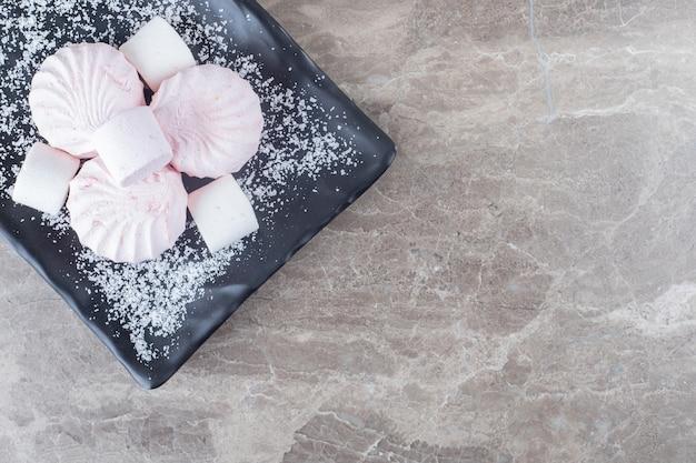 Pila di biscotti e marshmallow su un piatto da portata su una superficie di marmo
