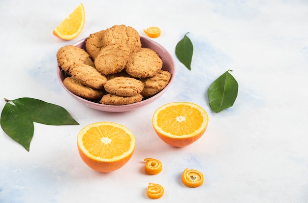 Pile of cookies in pink bowl and half cut oranges with leaves over white table.
