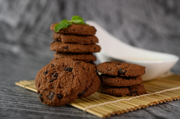 A pile of cookies and a spoon of milk on a cloth on a wooden table