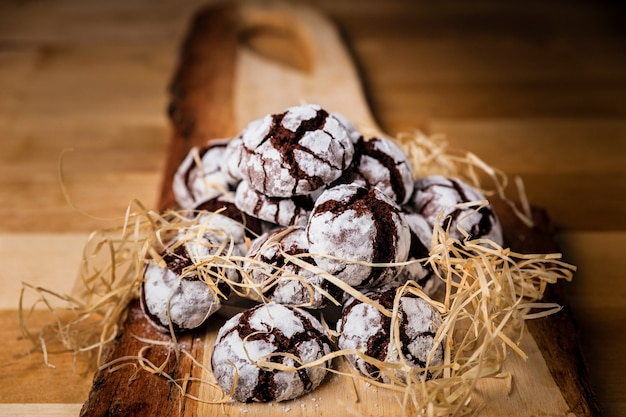 A pile of cracked cookies on wooden board