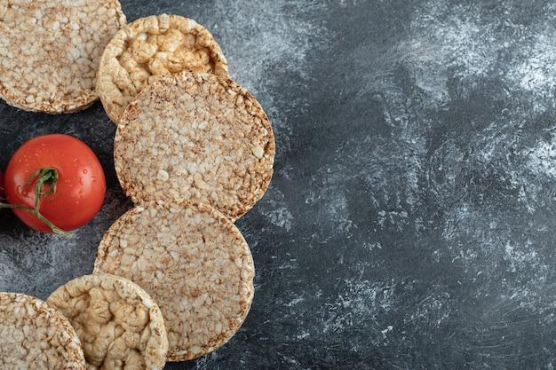 Pila di fette biscottate e pomodoro fresco sulla superficie in marmo