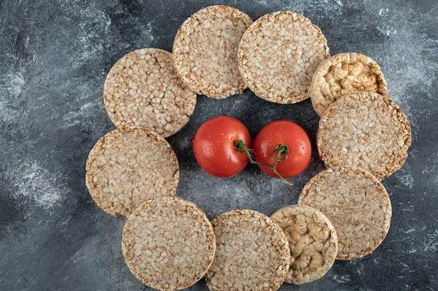 Pila di fette biscottate e pomodori freschi sulla superficie in marmo