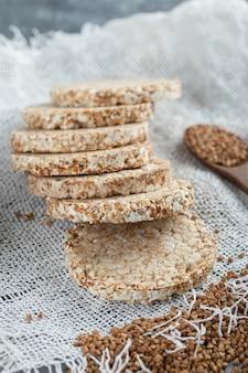 Pila di pane croccante e grano saraceno crudo su tela bianca