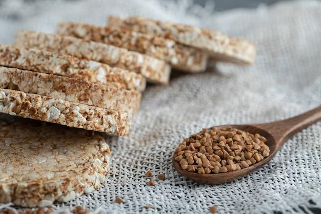 Mucchio di fette biscottate e cucchiaio di grano saraceno su tela bianca