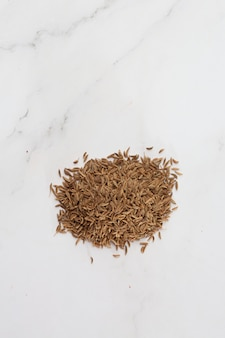Pile of cumin seeds captured from above isolated on white. seeds of caraway, also known as meridian fennel and persian cumin. aromatic carminative. concept of health and food