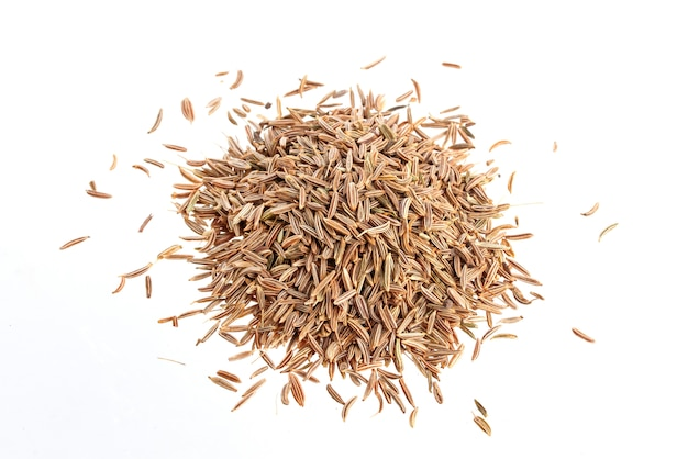 Pile of cumin seeds on white surface