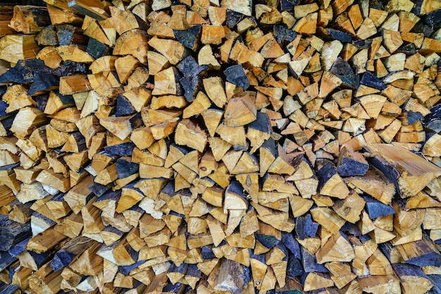 Pile of cut and stacked firewood in various colors. background.