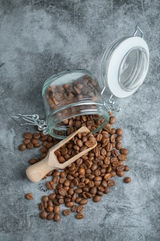 Pile of dark roasted coffee beans on marble surface