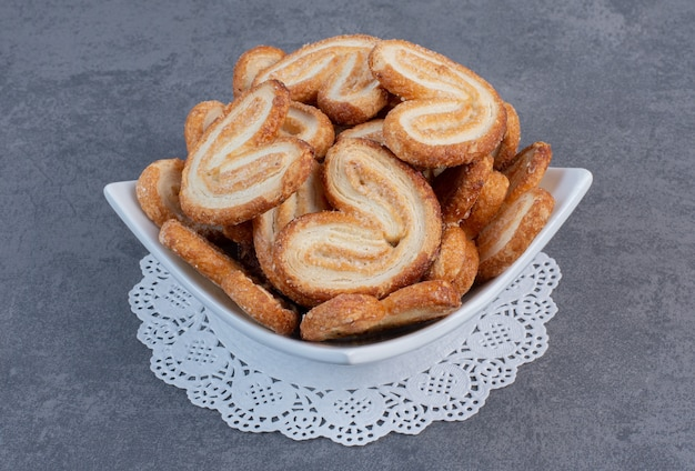 Pile of delicious biscuits in white bowl.