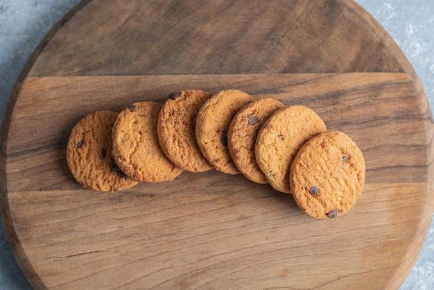 Pila di deliziosi biscotti con scaglie di cioccolato su tavola di legno