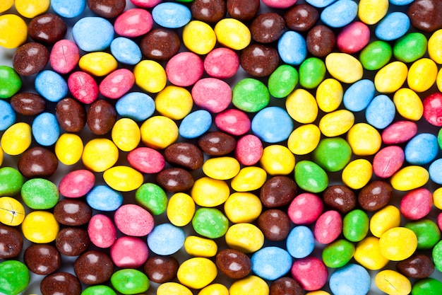 Pile of delicious rainbow colorful chocolate candies background