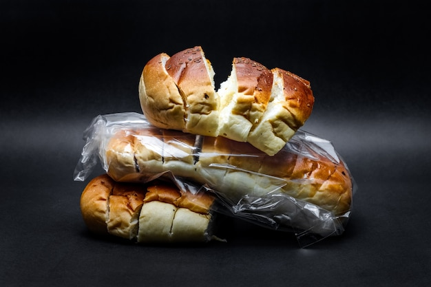 A pile of delicious wheat bread close view on a rough dark background
