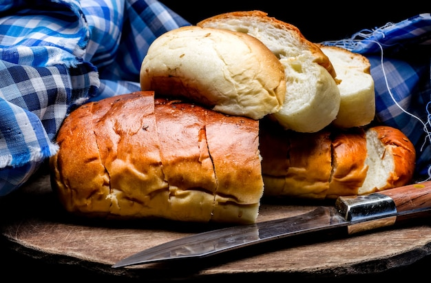 A pile of delicious wheat bread above a wooden chopping board with a knife and cloth on dark background