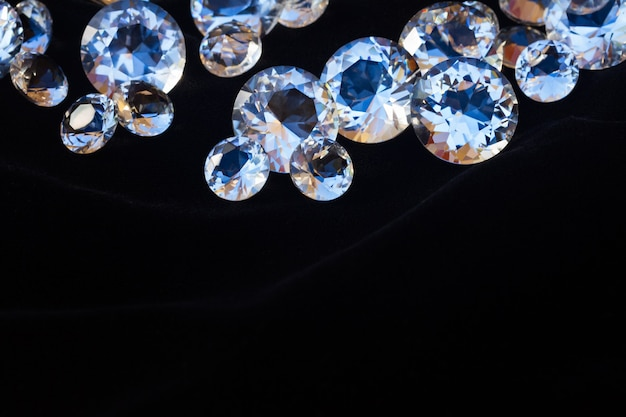 Pile of diamonds on black velvet background with copy space