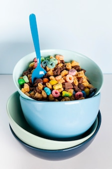 Pile of dirty blue bowls filled with cereal fruit loops
