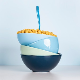 Pile of dirty blue bowls filled with cereals and spoon