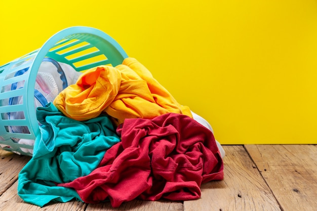 Pile of dirty laundry in washing basket on wooden plank yellow background.