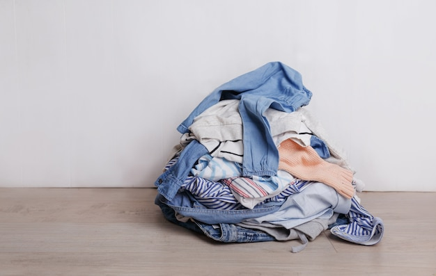 A pile of dirty multicolored clothes prepared for washing is lying on the floor in the light background