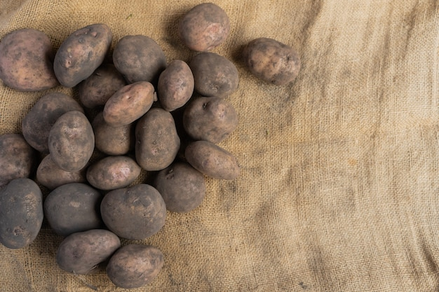 Pile of dirty potatoes on the left side of a jute mat