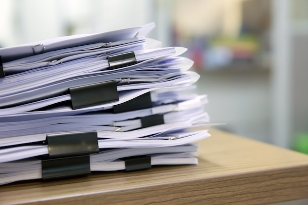 Pile of documents stack up on the table.