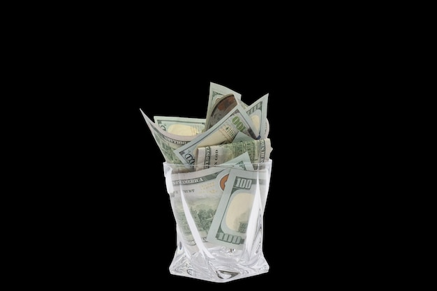 A pile of dollars stacked in a whiskey glass on a black isolated background
