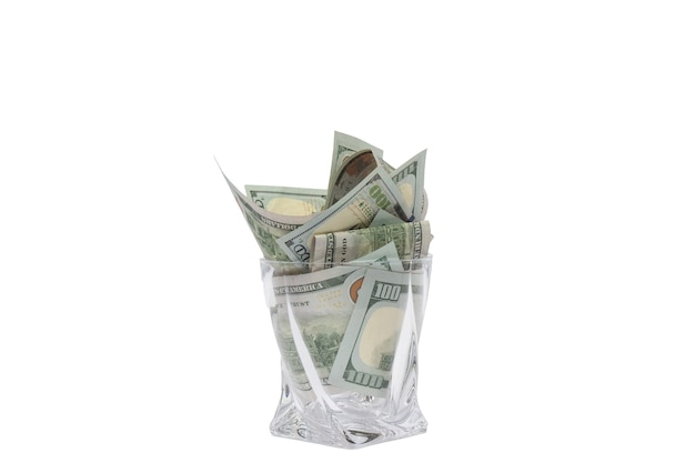 A pile of dollars stacked in a whiskey glass on a white isolated background