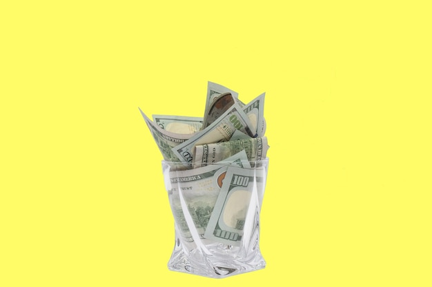 A pile of dollars stacked in a whiskey glass on a yellow isolated background