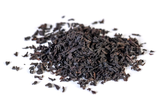 A pile of dried black tea leaves on a white. energetic drink.