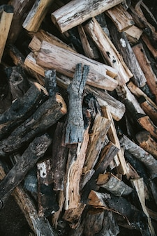 Pile of dried and burnt wood fire logs for fire camp in the akha village of maejantai on the hill in chiangmai, thailand.