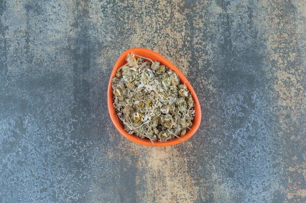 Mucchio di camomilla essiccata in una ciotola arancione.