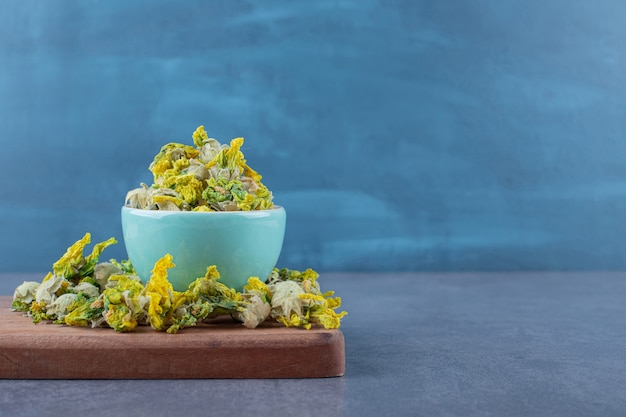 Pile of dried flowers on wooden board and in bowl.