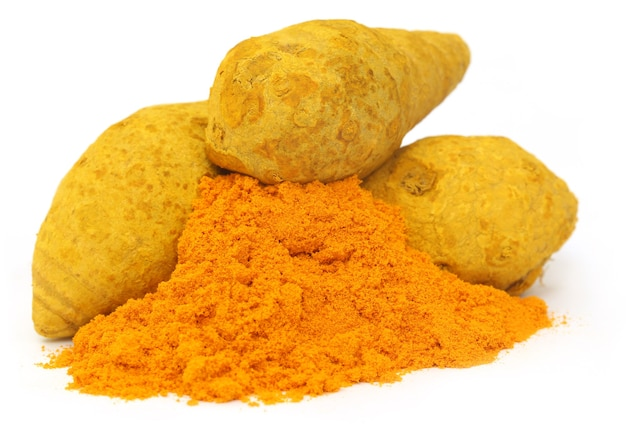 Pile of dried and ground turmeric over white background
