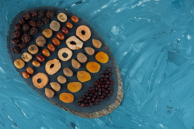 Pile of dried tropical fruits placed on a wooden board .