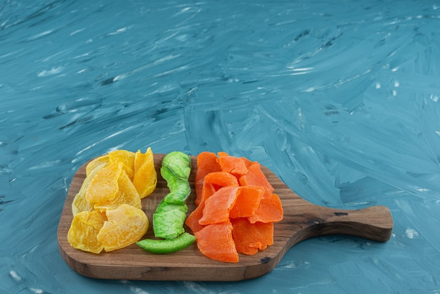 Pile of dried tropical fruits placed on a wooden cutting board .