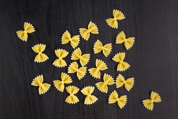 A pile of farfalle pasta on dark black background
