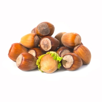 Pile of filbert nuts with green leaf isolated on white