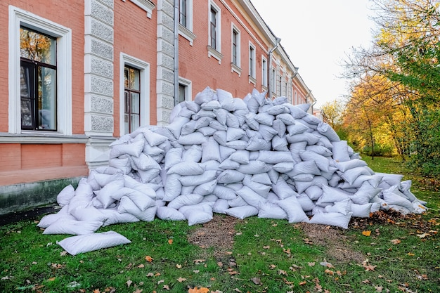Pile of filled construction bags lie in front of the building