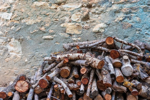 Pile of firewood stacked with a rustic wall