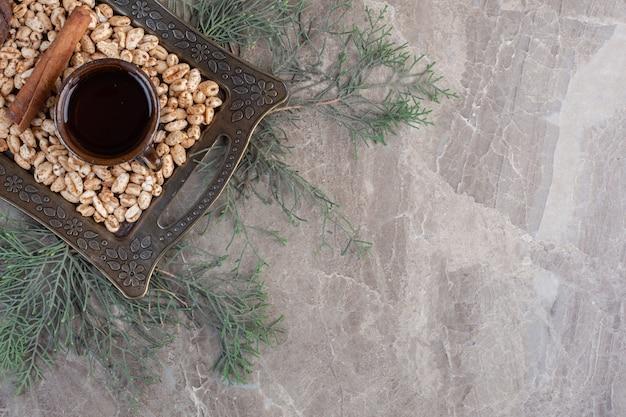 Pila di fiocchi con una stecca di cannella e una tazza di tè in un vassoio su foglie di pino su marmo.