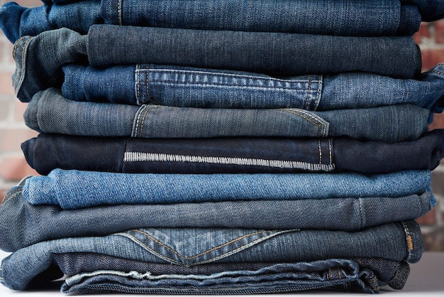 A pile of folded pairs of jeans