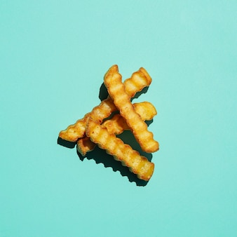 Pile of french fries on turquoise background