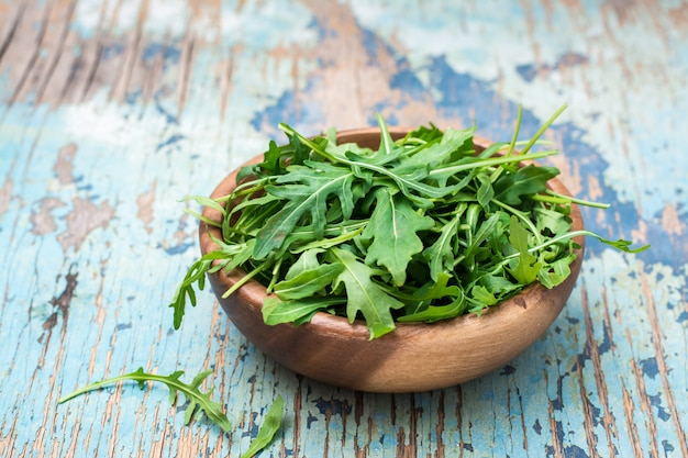 A pile of fresh arugula leaves in a wooden bowl on a wooden table